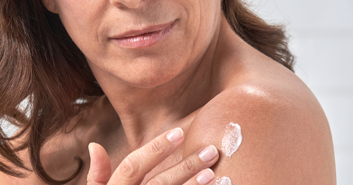 image of woman applying lotion to shoulder